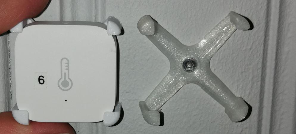 Hållare till Xiaomi Aqara temperatursensor i transparent till höger och vit till vänster.